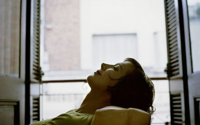 A woman lying back in a chair with her eyes closed.