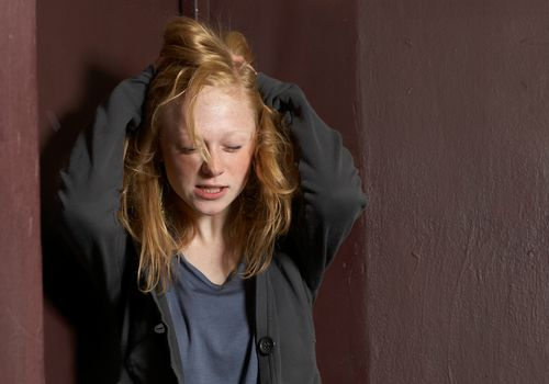 Young woman pushing hands through hair, eyes closed
