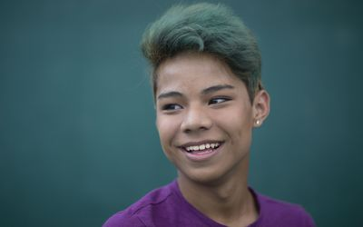 A young, transgender person of color with short hair colored green smiles and looks away from the camera. They are wearing a purple shirt