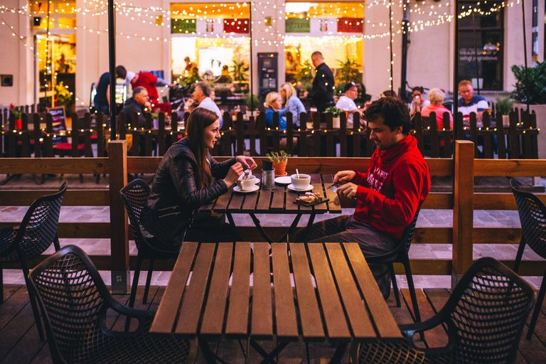 white man and white woman having coffee on a patio