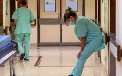 A nurse in blue scrubs leans against a wall.