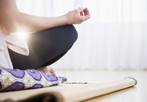 woman meditating on yoga mat