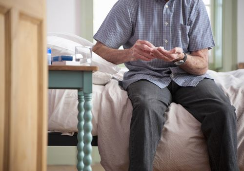 Older man taking pills on bed