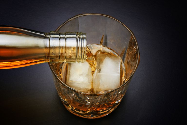Pouring whiskey in nice glass with ice
