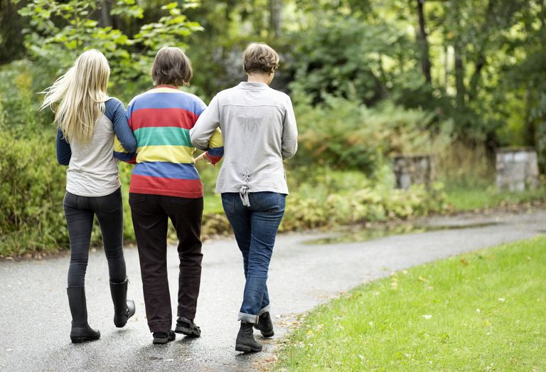 Rear view of three generation females walking on path at park