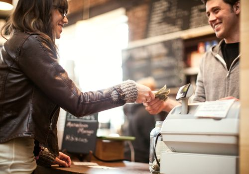 A happy woman hands a smiling cashier a few dollars at a coffee shop.
