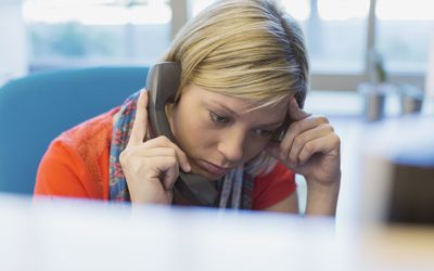 Worried businesswoman using telephone at work