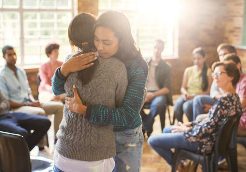 Women hugging in a support group meeting