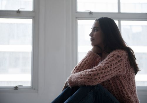 Hispanic woman wearing pink sweater and jeans near window