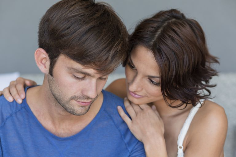 woman resting her chin on man's shoulder