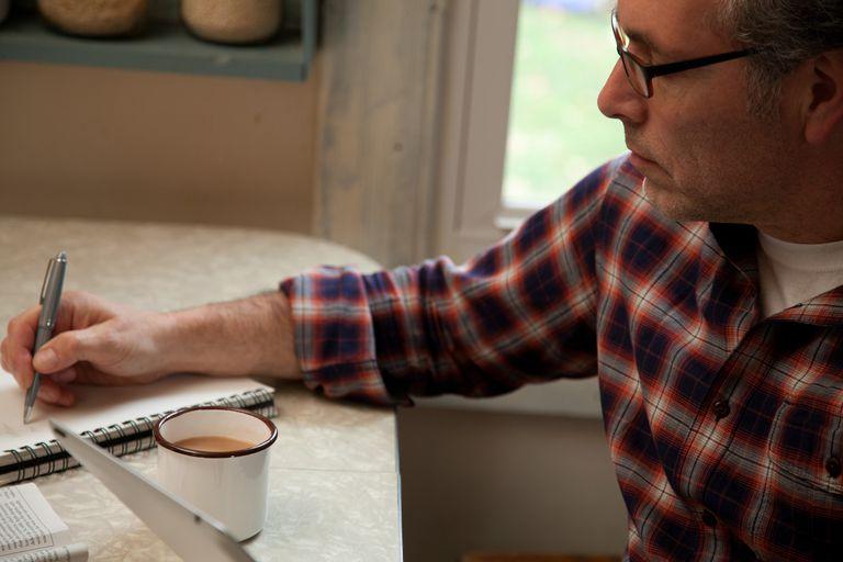 mature man writing at table