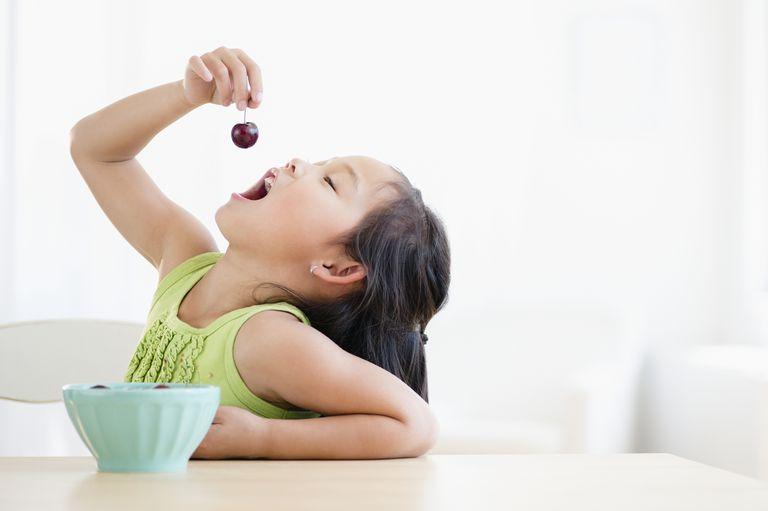 Girl eating cherries.