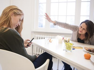 Woman ignores companion while she looks at her phone