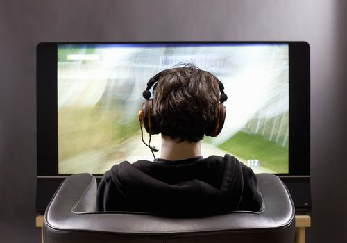 The back of a young man's head wearing headphones in front of a TV