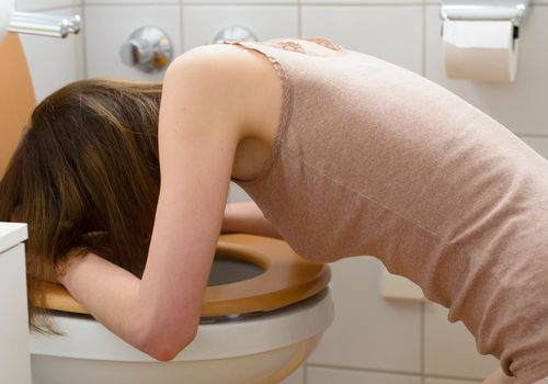 Woman bent over a toilet throwing up