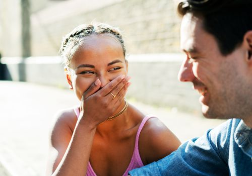 Woman in pink dress laughing at something male companion says