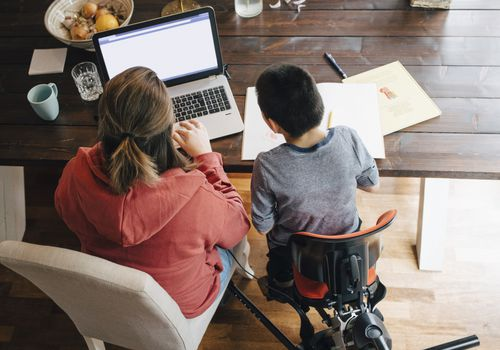 High angle view of mother with autistic son watching video on laptop while sitting at home
