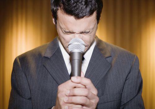 Man closing eyes behind microphone