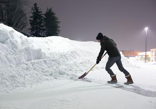 Man pushing snow with a shovel toward a snow bank at night.