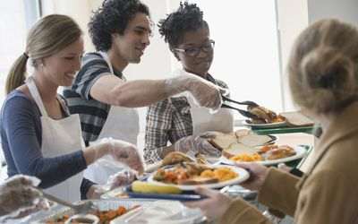 people serving food in buffet line