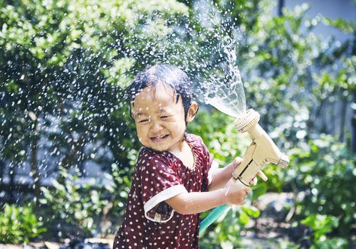 Little girl spraying water hose