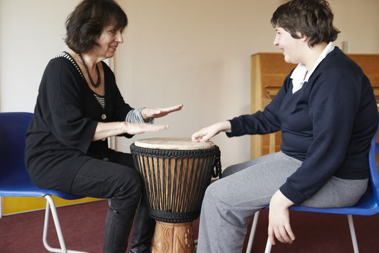 teacher and student playing drum during music therapy