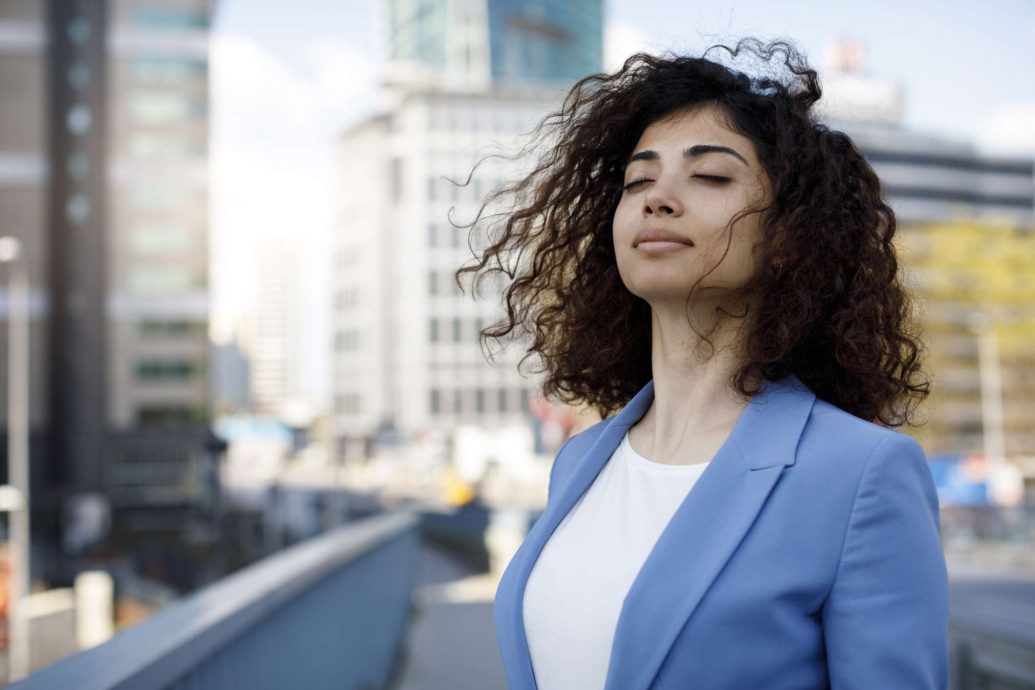 Businesswoman closing her eyes and taking a deep breath while standing downtown