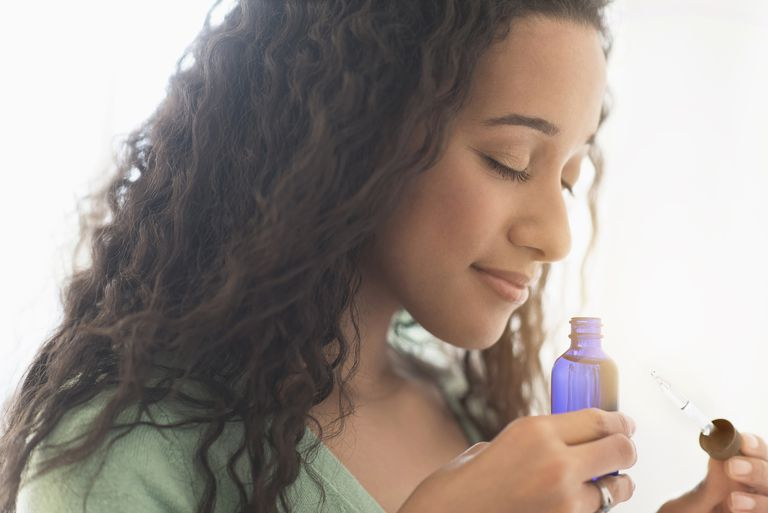 mixed race woman smelling aromatherapy oil bottle