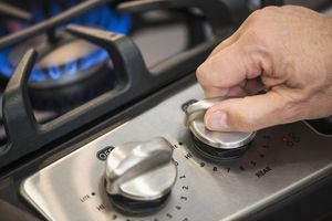 Close-up of a hand turning off a gas stove