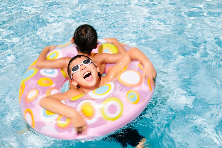Two young boys floating in inflatable pool toy