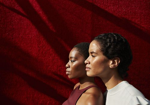 Side view of women standing against red wall
