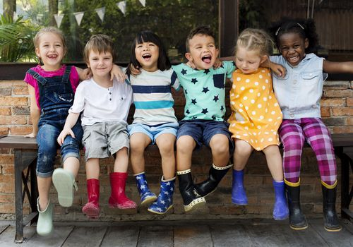 children sitting on a bench and smiling