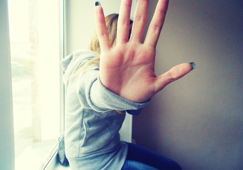 Woman sitting on window sill holding her hand up to the camera to block her face