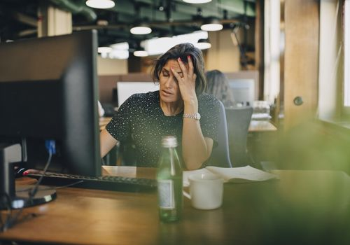 Upset woman with her hand on her head at her office desk