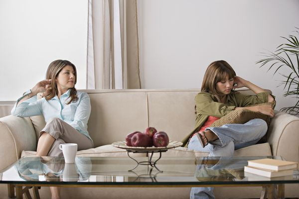 upset women sitting on opposite sides of couch