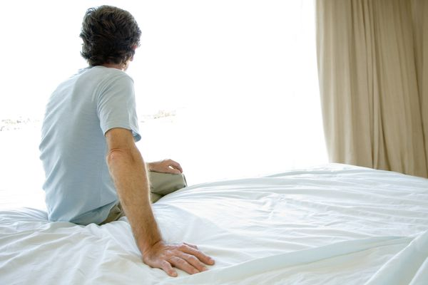 Mature man sitting alone on bed