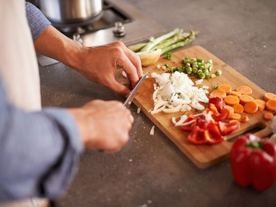 Cropped shot of a man chopping vegetables on a countertop.
