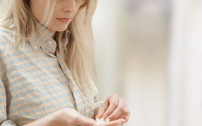 Woman with handful of drugs