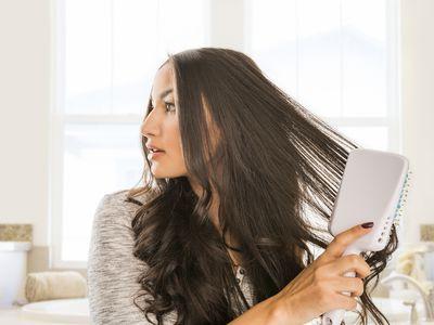Woman brushing long dark, wavy hair with a large, flat hairbrush