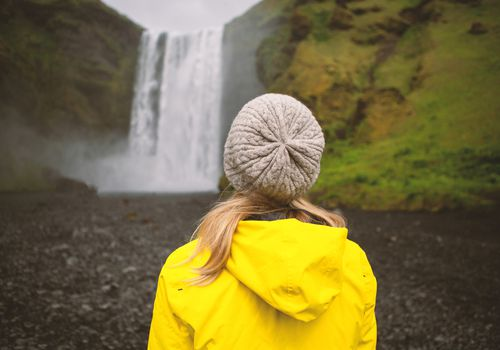 Young woman contemplating waterfall