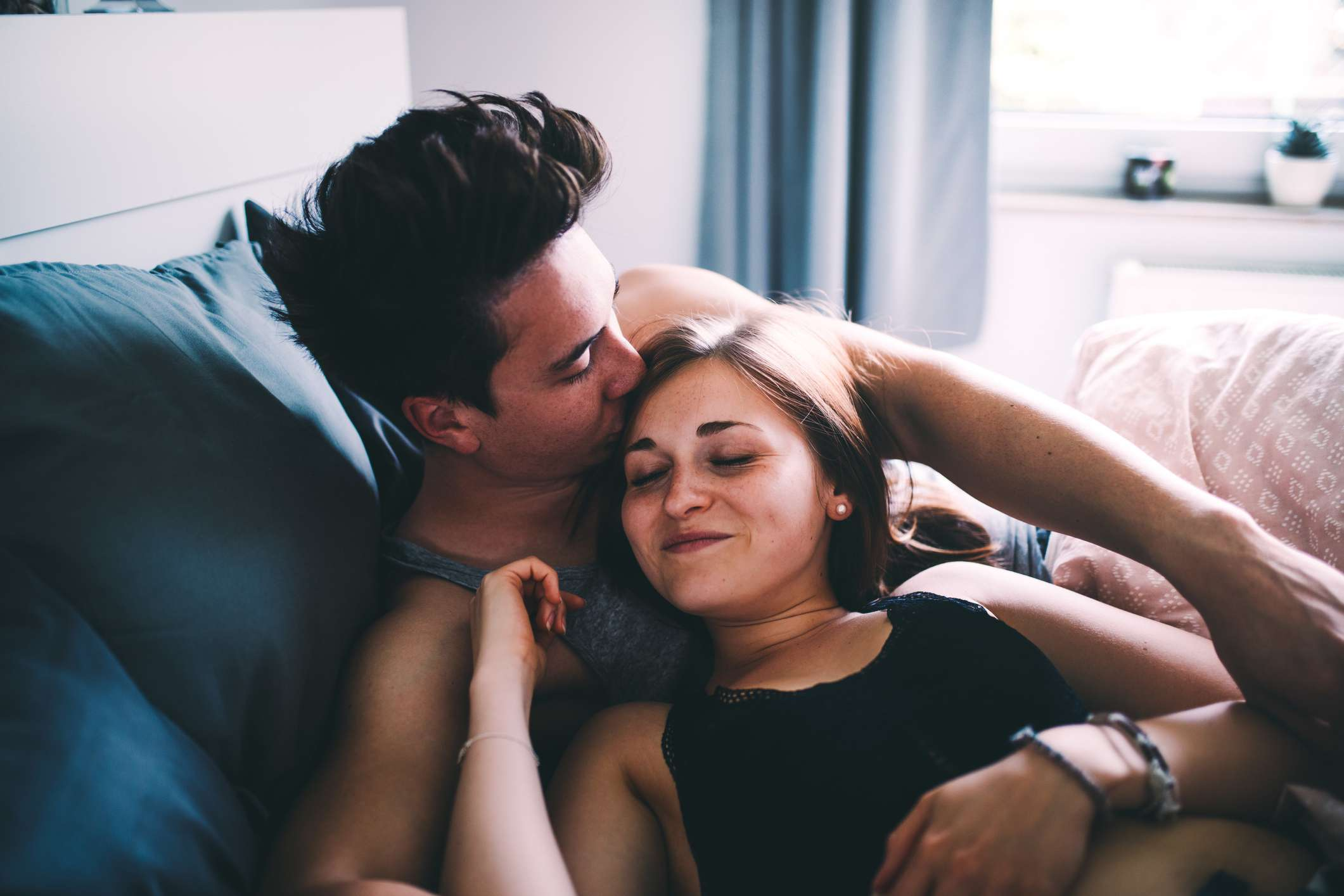 Young man kissing a woman's forehead in bed