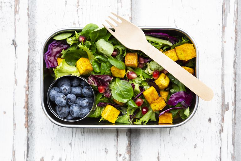 Mixed salad with roasted tofu, red cabbage, pomegranate seeds, blueberries and curcuma in lunch box