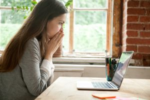 young woman upset looking at laptop