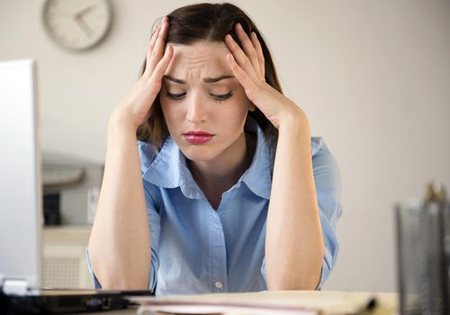 stressed woman with her head in her hands at work desk