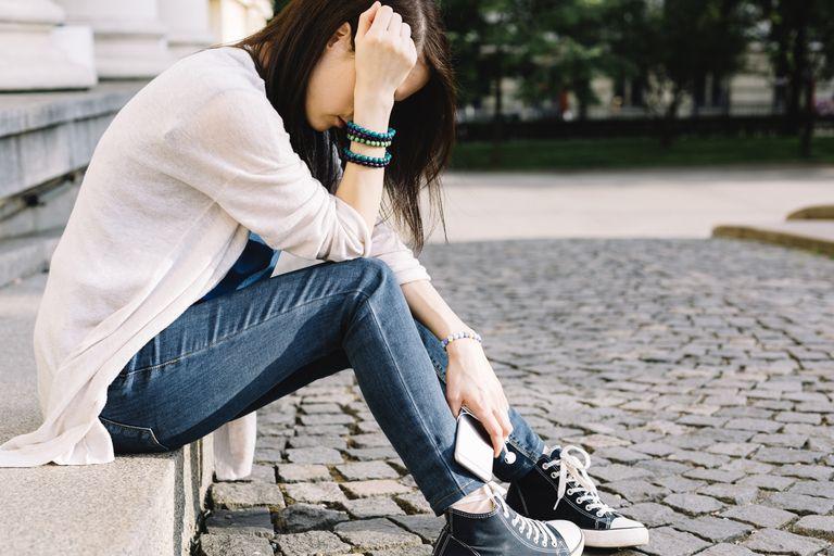 Depressed girl sitting at the street