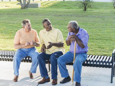 Three multi-ethnic senior men sitting on bench talking
