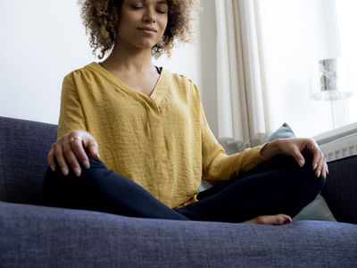 Young woman sitting on couch at home meditating
