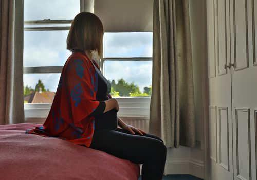 Lone pregnant woman sitting on the bed looking out at the window in the morning