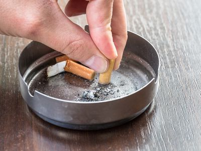 a person putting a cigarette out in an ashtray