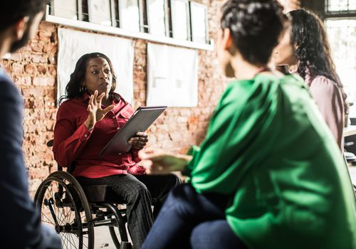 A black person using a wheelchair gives a presentation to colleagues at work.